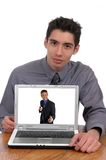 Internet Swindle. A man pointing to a laptop screen picturing a man extending money with a string attached Stock Photography