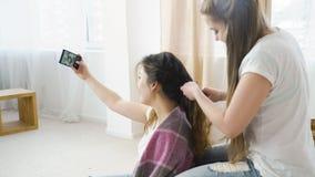 Selfie addiction hair braiding friends leisure. Internet technology online social network addiction. selfie posting youth lifestyle. girlfriends hair braiding Royalty Free Stock Image