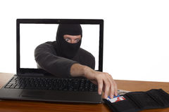 Internet Theft. Concept online theft - a man wearing a ski mask reaching through laptop screen to steal wallet stock image