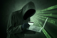 Internet Theft Concept. Man holding credit card with laptop on his hand royalty free stock photography