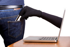 Internet Theft. A gloved hand reaching through a laptop screen to steal a credit card from a man's pocket stock photo