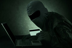 Internet Theft. A man wearing a balaclava and holding a credit card while sat behind a laptop Stock Photos