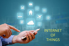 Internet of things (IOT) concept. Businessman holding and using. Smart phone and wireless communication network, represented by symbol connected with icons of Royalty Free Stock Photo