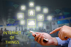 Internet of things (IOT) concept. Businessman holding and using. Smart phone and wireless communication network, represented by symbol connected with icons of Stock Photography