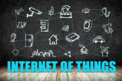 Internet of Things (IoT) word on wood floor with doodle icon on Stock Images