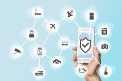 Internet of things security concept with hand holding modern smart phone to control intruders into a network of objects.  Stock Photos