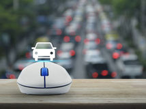 Internet transportation service concept. Car flat icon with wireless computer mouse over blur of rush hour with cars and road, Internet transportation service Stock Photos