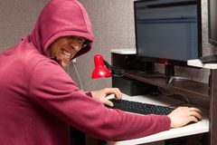 Internet troll with the evil face using a computer. Very bad man laughs wickedly writing nasty things on the forum. Internet troll with the evil face using a stock photo
