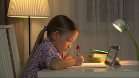 Internet Usage on Tablet, Child Writing, Girl Studying for School, Night View 4K.  stock video