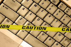 Internet warning. Dirty laptop keyboard close up shot on an angle caution tape acrossed the keyboard Stock Photography