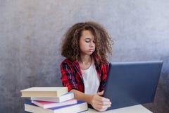 Internet websurfing de la muchacha adolescente del pelo rizado en el ordenador portátil en casa Fotografía de archivo