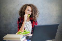 Internet websurfing de la muchacha adolescente del pelo rizado en el ordenador portátil en casa Fotos de archivo