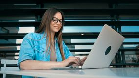 Internet Work with Laptop. Casual stylish cheerful girl wears jeans scirt works with laptop computer near modern building wall outdoor, slowmotion stock video footage
