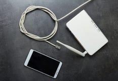 Interneta kabel z włącznikiem rj45, router używać sieć bezprzewodową i smartphone, na szarość fotografia stock