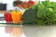 Interni della cucina Molte verdure e l'altro pasto alla tavola di vetro sono pronti per cucinato presto Immagine Stock
