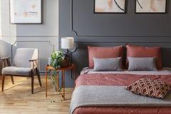 Interno accogliente della camera di albergo con un letto matrimoniale con i cuscini accanto a Fotografie Stock Libere da Diritti