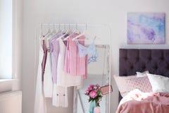 Interno alla moda della camera da letto con lo scaffale dei vestiti Fotografie Stock Libere da Diritti
