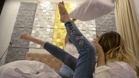 Interno alla moda e moderno della stanza Tre ragazze stanno combattendo allegro sul letto bianco Camice ed occhiali da sole bianc stock footage