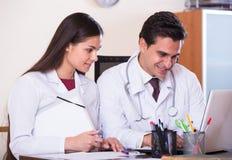 Interno asesor de los jóvenes del doctor en oficina de la clínica Fotos de archivo libres de regalías