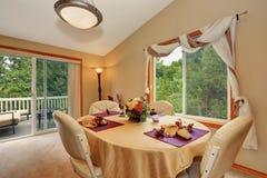 Interno beige molle della sala da pranzo con la tavola piacevolmente decorata immagini stock