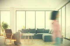 Interno bianco con un sofà grigio, ragazza del salone Fotografie Stock