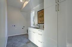 Interno bianco della stanza di lavanderia con i gabinetti ed il pavimento piastrellato grigio immagini stock libere da diritti