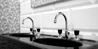 Interno in bianco e nero del bagno con il lavandino nero due ed il rubinetto classico di stile Immagini Stock