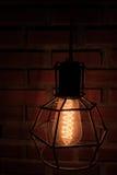 Interno d'annata della casa della decorazione di illuminazione di lampadina con il fondo del muro di mattoni Fotografia Stock Libera da Diritti