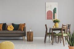 Interno d'annata della sala da pranzo e di vita con la retro tavola con le sedie ed il sofà comodo con i cuscini fotografia stock