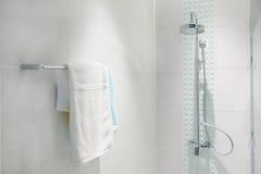 Interno del bagno con la testa di doccia moderna e l'asciugamano bianco Immagini Stock Libere da Diritti
