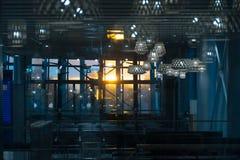 Interno del corridoio dell'aeroporto nella sera, attraverso il vetro panoramico i raggi del passaggio del sole Immagine Stock