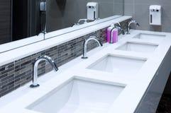 Interno del lavandino della toilette della toilette pubblica con delle mani di lavaggio Fotografie Stock Libere da Diritti