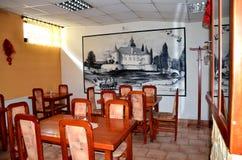 Interno del ristorante che contiene mobilia di legno e verniciatura del castello della città storica sulla parete Immagini Stock