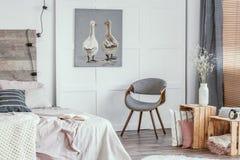 Interno delizioso della camera da letto con la sedia grigia alla moda fotografia stock libera da diritti