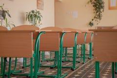 Interno dell'aula vuota con le sedie e gli scrittori in una fila fotografia stock libera da diritti