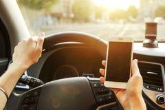 Interno dell'automobile con l'autista femminile che si siede dietro la ruota, luce molle di tramonto Cruscotto lussuoso ed elettr immagini stock