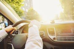 Interno dell'automobile con l'autista maschio che si siede dietro la ruota, luce molle di tramonto Cruscotto lussuoso ed elettron fotografie stock libere da diritti