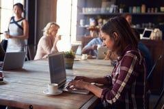 Interno della caffetteria con i clienti che per mezzo dei dispositivi di Digital fotografie stock