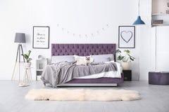 Interno della camera da letto con il letto comodo immagini stock libere da diritti