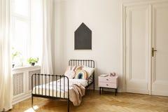 Interno della camera da letto del bambino con un letto singolo, una finestra e una lavagna su una parete immagine stock libera da diritti