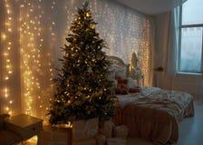 Interno della camera da letto, per il nuovo anno e decorato con un albero di Natale ed i regali Caduta luminosa delle ghirlande s Fotografie Stock