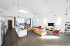 Interno della casa con il salotto aperto di piano e l'area pranzante Immagine Stock Libera da Diritti