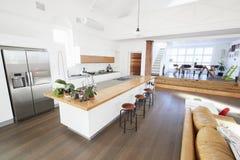 Interno della casa con la cucina aperta di piano e l'area pranzante Fotografie Stock