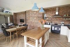 Interno della casa con la cucina aperta di piano, il salotto e l'area pranzante Immagini Stock