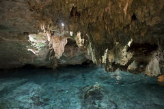 Interno della caverna della pietra con acqua blu e rocce Immagine Stock
