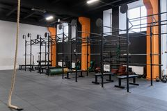 Interno della palestra per l'allenamento di forma fisica con la barra orizzontale, i bilancieri e la corda Immagini Stock