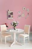 Interno della sala da pranzo con la parete rosa dei piatti decorativi dei fiori Fotografia Stock