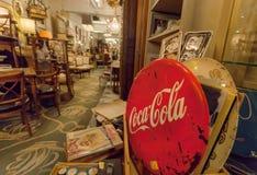 Interno della stanza antica del mercato con la pubblicità di Coca-Cola, i libri, i ricordi e la retro mobilia Fotografie Stock