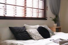 Interno della stanza con i ciechi comodi di finestra e del letto matrimoniale immagine stock