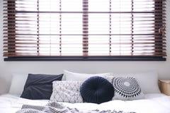 Interno della stanza con i ciechi comodi di finestra e del letto matrimoniale immagini stock